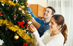 Man and woman decorating Christmas tree Stock Photography