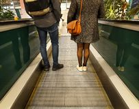 Man and Woman descend escalator on shopping mall. Feet, shoes, backpack, purse. Back view royalty free stock image