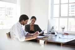 Man and woman at a desk in an office looking at documents Stock Photo