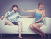 Man and woman in disagreement sitting on sofa Royalty Free Stock Image