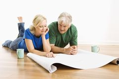 Man and woman discussing blueprints. Stock Images