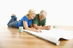 Man and woman discussing blueprints. Royalty Free Stock Images
