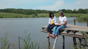 Man and woman and discussing  books on the board table near lake stock video footage