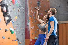 Man and woman discussing by climbing wall in crossfit gym Stock Photo