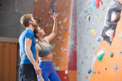 Man and woman discussing by climbing wall in crossfit gym Royalty Free Stock Image