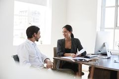 Man and woman discussing documents at a desk in an office Stock Photos
