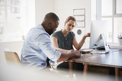 Man and woman discussing documents at her desk in an office Stock Photo