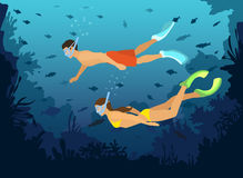 Man and Woman diving snorkeling exploring underwater world with fishes, corals, reefs Royalty Free Stock Photos