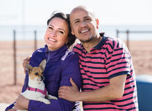 man, woman and dog on the beach Royalty Free Stock Image