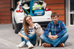The man and woman with dog by car ready for car trip. Happy young couple,woman with long hair,sun glasses,striped t-shirt and blue jeans and the dark hair men in Stock Photography