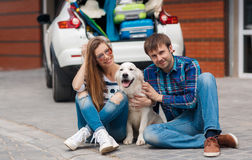 The man and woman with dog by car ready for car trip. Happy young couple,woman with long hair,sun glasses,striped t-shirt and blue jeans and the dark hair men in Royalty Free Stock Photo