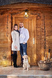 Man and woman with dog in front of wooden cottage Stock Photos