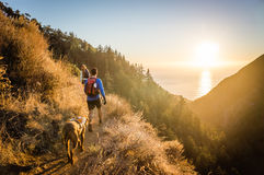 Man, woman, and dog hiking at sunset. Royalty Free Stock Image