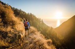 Man, woman, and dog hiking at sunset. Royalty Free Stock Image