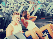 Man and woman doing abs exercise in gym. Well trained men coach assisting cheerful girl to make abs exercise sit ups in gym indoors . Focus on man Stock Photo
