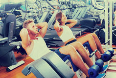 Man and woman doing abs exercise in gym. Well trained men coach assisting cheerful young women to make abs exercise sit ups in gym indoors . Focus on man Royalty Free Stock Photography
