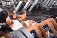 Man and woman doing abs exercise in gym. Young men coach assisting cheerful smiling girl to make abs exercise sit ups in gym indoors. Focus on woman Stock Photography