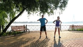 Man and woman doing exercise and start running stock video