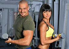 Man and woman are doing exercises in a sport club. Royalty Free Stock Images