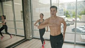 A man and woman doing fitness in the studio - endurance training. Mid shot stock footage