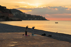 Man and woman doing gymnastics on the beach of Nice, France Royalty Free Stock Photos