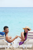 Man and woman doing honeymoon in cuba. Husband and wife relaxing on sunbeds on the beach and smiling at camera. Vertical shape, rear view, copy space Stock Photography
