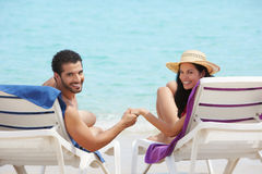 Man and woman doing honeymoon in cuba. Husband and wife relaxing on sunbeds on the beach and smiling at camera. Horizontal shape, rear view, copy space Stock Photo