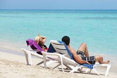 Man and woman doing honeymoon in cuba. Husband and wife relaxing on sunbeds on the beach and smiling. Horizontal shape, side view, copy space Royalty Free Stock Photos