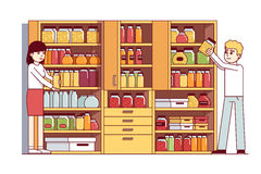 Man and woman doing housework in pantry or cellar. Man and woman, husband, wife doing housework in home pantry or cellar. Big cupboard full of jars, boxes Royalty Free Stock Images