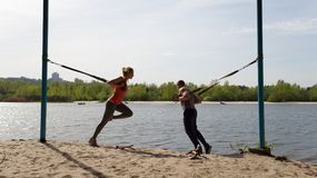 Man and woman doing lunge exercises with TRX gear. Stock Photos