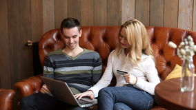 Man and woman doing online shopping. Young positive man and woman using laptop and doing online shopping while sitting on the brown sofa in the cafe stock footage