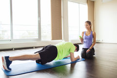 Man and woman doing plank exercise on mat in gym Stock Photo
