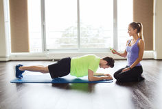 Man and woman doing plank exercise on mat in gym. Fitness, sport, technology and people concept - men and women with smartphone doing plank exercise on mat in royalty free stock images