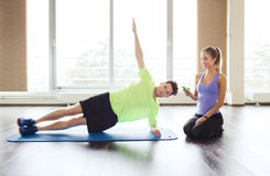 Man and woman doing plank exercise on mat in gym. Fitness, sport, technology and people concept - men and women with smartphone doing side plank exercise on mat stock photography