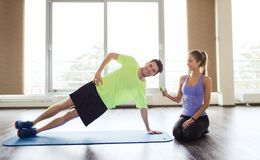 Man and woman doing plank exercise on mat in gym Stock Image