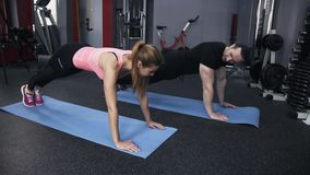 Man and woman doing a plank in a gym stock video