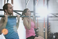 Man and woman doing pull ups in crossfit gym Stock Photography
