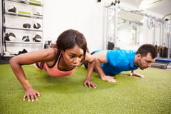 Man and a woman doing push ups at a gym. Man and a women doing push ups at a gym Stock Photography
