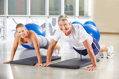 Man and woman doing push ups in a gym. Man and women doing push ups together in a gym Royalty Free Stock Photo