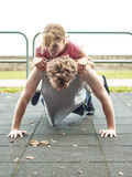 Man and woman doing push ups outdoor. Royalty Free Stock Images