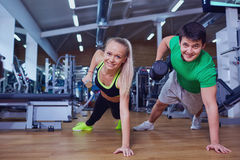 Man and woman doing pushups with dumbbells in his hands on in th Royalty Free Stock Photo
