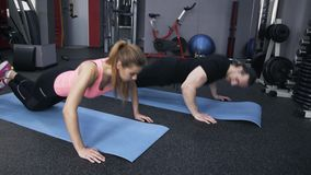 Man and woman doing pushups in a gym stock video footage