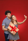 Man and woman doing selfie phone Pin Up with a gift in style, is Royalty Free Stock Photos