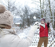 Man and woman doing a snowball fight Royalty Free Stock Photo