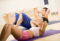 Man and woman doing stomach crunches Stock Photo