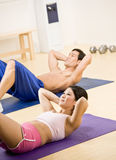 Man and woman doing stomach crunches Stock Photos