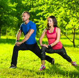 Man and woman doing stretching exercises stock photos