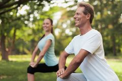 Man and woman doing warm-up in nature. Couple doing sports in nature. Stock Photo