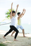 Man and Woman doing yoga on beach. Royalty Free Stock Photo