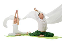 Man and woman doing yoga exercises in studio. Man and women doing yoga together sitting in splits on green mats in studio white cloth flying around Royalty Free Stock Photo